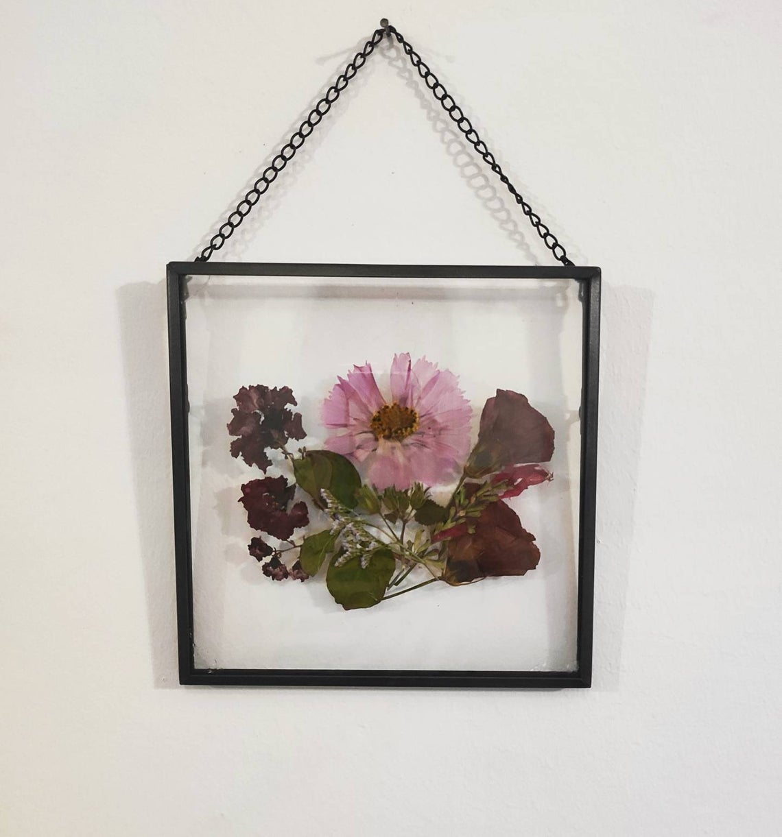 Pink pressed flowers in a floating brass frame